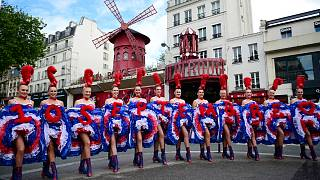 Dancers from the Moulin Rouge cabaret pose for photographers, on May 17, 2021 in Paris
