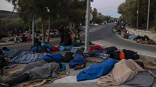 In this Thursday, Sept. 10, 2020, file photo, refugees and migrants sleep on a street near the destroyed Moria camp following a fire, on Lesbos island, Greece.