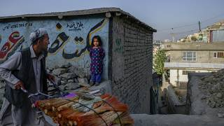 A vendor pushes his handcart loaded with brooms as a girl watches in Kabul.
