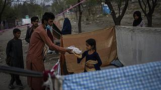 Displaced Afghans distribute food donations at an internally displaced persons camp in Kabul, Afghanistan, Monday, Sept. 13, 2021.