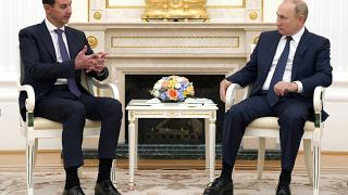 Russian President Vladimir Putin, right, sits with Syrian President Bashar Assad