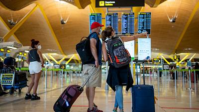 Passengers check the departure screen at Adolfo Suarez-Barajas airport in Madrid, Spain, July 9, 2021.