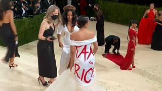 """La congresista hispana Alexandra Ocasio-Cortez posa ante la prensa con un vestido blanco sobre el que está escrito en letras rojas """"cobren impuestos a los ricos"""""""
