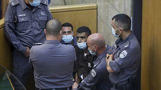زكريا الزبيدي، أحد الفلسطينيين الستة الذين فروا من سجن جلبوع، محاط بالحراس في قاعة محكمة في مدينة الناصرة بإسرائيل، يوم السبت 11 سبتمبر 2021