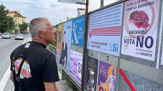 Un homme regardant la campagne d'affichage choc des anti et pro-IVG à Saint-Marin, 10 septembre 2021