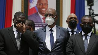 Haiti's Prime Minister Ariel Henry (C) in front of a portrait of slain Haitian President Jovenel Moise at the National Pantheon Museum Port-au-Prince, Haiti, July 20, 2021.