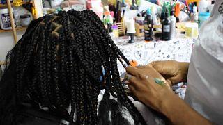 Estilista venezolana trenzando pelo afro, 17/08, 2021, Caracas, Venezuela