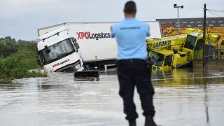A French Gendarme officer looks at two trucks blocked in a flooded road in Codognan, in the Gard department, in the Occitanie region, southern France, on September 14, 2021