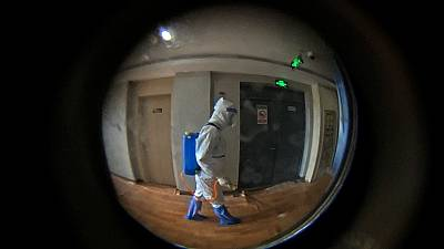 A medical worker wearing a protective clothing disinfectants a corridor of a hotel used for foreigners to stay during a period of health quarantine
