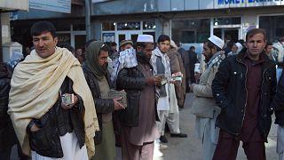 صرافون أفغان ينتظرون العملاء في سوق صرف العملات في كابول، أفغانستان، 17 ديسمبر 2015