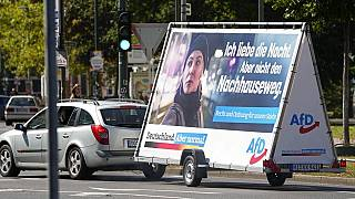In this Wednesday, Aug. 25, 2021 file photo a car pulls an election poster for the right wing party 'Alternative for Germany' (AfD) at a street in Duesseldorf, Germany.