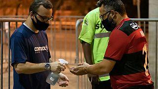 Adepto desinfeta mãos à entrada do Estádio do Maracanã, Rio de Janeiro