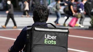 In this April 28, 2021, file photo, an Uber Eats delivery person rides a bicycle while delivering food