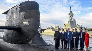 الرئيس الفرنسي إيمانويل ماكرون ورئيس الوزراء الأسترالي مالكولم تورنبول يقفان مع مسؤولين في الحكومة الأسترالية، فوق غواصة تابعة للبحرية الملكية الأسترالية ، سيدني 2 مايو 2018