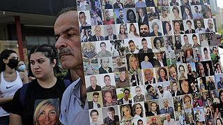 لافتة تظهر وجوه ضحايا انفجار مرفأ بيروت بينما تجمع محتجون وأفراد عائلات الضحايا في مظاهرة بالقرب من قصر اليونسكو في بيروت - 12 أغسطس 2021