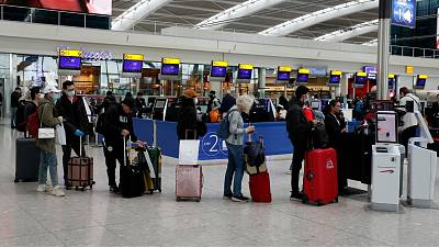 People queue at ticket machines at Heathrow airport in London, Wednesday, March 18, 2020.
