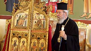 The leader of Cyprus Orthodox Church, Archbishop Chrysostomos II, stands next to the reclaimed doors at the Archbishopric in Nicosia on Thursday