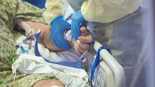 ABD'de yoğun bakımdaki Covid-19 hastasının nabzını alan bir doktor (arşiv)