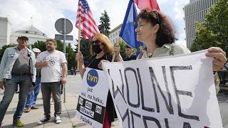 محتجون يقفون خارج البرلمان البولندي للاحتجاج على خطط الحكومة للتصويت على مشروع قانون لوسائل الإعلام يُنظر إليه على أنه يقيد استقلال وسائل الإعلام/ وارسو، بولندا/ 11 أغسطس 2021