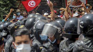 متظاهرون تونسيون يواجهون عناصر الشرطة خلال مظاهرة في تونس العاصمة في 25 تموز/يوليو 2021