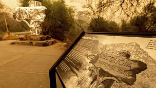 Fire-resistant wrap covers a historic welcome sign as the KNP Complex Fire burns in Sequoia National Park, Calif., on Sept. 15, 2021.