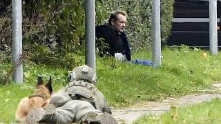 A police office watches Peter Madsen as he sits on the side of a road after being apprehended following a failed escape attempt in Albertslund, Denmark, Oct. 20, 2020.