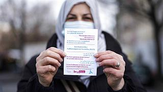 Aliye Tuerkyilmaz a member of a multilingual team of five street workers shows an information flyer as she poses for a photo in Berlin, Germany, Tuesday, March 9, 2021.