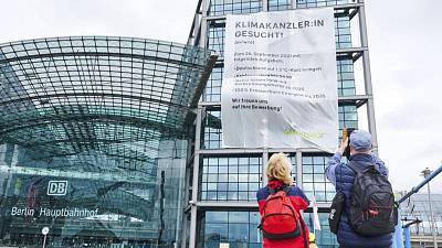 """Greenpeace activists hanging a large banner reading """"Climate Chancellor wanted!"""" at Berlin's main train station in Berlin, Germany, Friday, Sept. 17, 2021."""