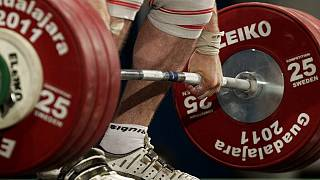 An athelete lifts 185 kg in the clean and jerk of a men's 105 kg weightlifting competition.