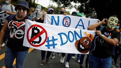 People take part in a protest against the use of Bitcoin as legal tender and legal reforms to extend president Nayib Bukele's term in San Salvador, September 15, 2021.
