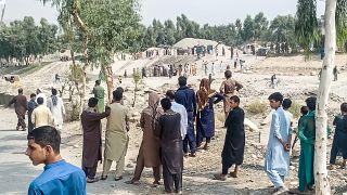عناصر من طالبان ومدنيون يتجمعون في موقع انفجار قنبلة استهدفت شاحنة صغيرة تقل مقاتلي الحركة في جلال آباد في 19 أيلول/سبتمبر 2021