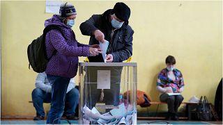 روسيان يدليان بأصواتهما للانتخابات البرلمانية في مدينة سان بطرسبورغ يوم الجمعة 17 أيلول/سبتمبر