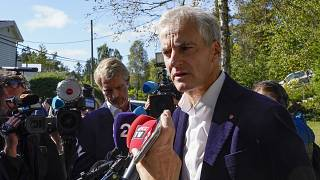Norway's Labor Party leader Jonas Gahr Store answers questions from reporters outside his home in Oslo.