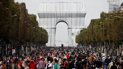 Pedestrians walking along the Champs-Elysees, in front of the Arc de Triomphe wrapped in silver by the late artist Christo.