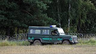 Polish border guards monitor an area along the border with Belarus in Usnarz Gorny, Poland.