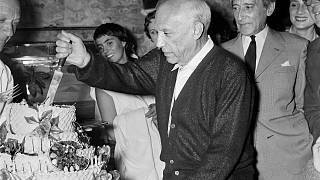 Spanish painter Pablo Picasso, flanked by his French friend poet Jean Cocteau (R), cuts his cake for his 75th birthday on October 25, 1956 in Vallauris.