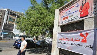 عراقي يمشي أمام اللوحات الإعلانية الانتخابية ولافتات المرشحين للانتخابات النيابية المقبلة في منطقة الكرادة بالعاصمة بغداد، 19 سبتمبر 2021