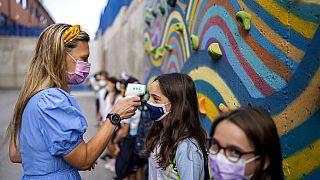 Tanár ellenőrzi a gyerekek hőmérsékletét egy madridi iskolában