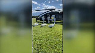 Militares con trajes de protección extraer varios cadáveres de guerrilleros del ELN de un helicóptero del Ejército colombiano