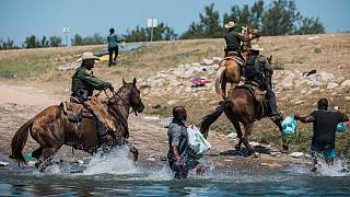 ضباط الجمارك وحماية الحدود الأمريكية يحاولون احتواء المهاجرين أثناء عبورهم ريو غراندي من سيوداد أكونيا في المكسيك إلى ديل ريو في تكساس.