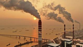 The sun sets near a coal-fired power plant on the Yangtze River in Nantong in eastern China's Jiangsu province on Dec. 12, 2018