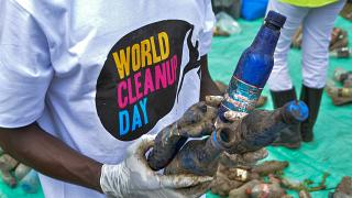 A World Cleanup Day volunteer collects and sorts plastic bottles removed from the River Wigwa in Kisumu, Kenya, Sept. 18, 2021.