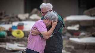 Dos hermanos lloran abrazados frente a la casa de sus padres, destruida por la inundación en Altenahr, Alemania, el lunes 19 de julio de 2021.