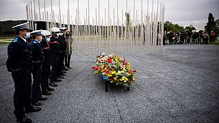Policemen and firemen stand at a monument dedicated to the victims of the explosion.