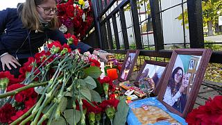 A student places a candle next to flowers and portraits of victims of shooting, outside the Perm State University following a campus shooting in Perm.