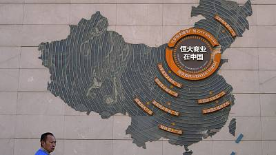 A custodian stands near a map showing Evergrande development projects in China on a wall in an Evergrande city plaza in Beijing, Tuesday, September 21, 2021.