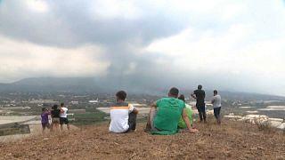 Habitantes evacuados de la isla de la Palma contemplan en la distancia como la lava destruye sus hogares