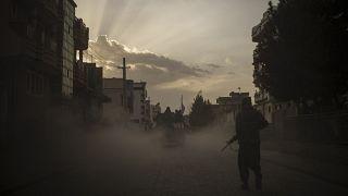 مقاتل من طالبان يمشي على جانب طريق فيما سيارة هامفي تحمل مقاتلين آخرين في كابل. 2021/09/21