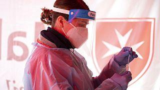 Eine Malteser-Mitarbeiterin wartet auf das Ergebnis eines Corona-Schnelltests
