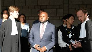 Mpanzu Bamenga, centre, stands with his legal team and rights activists outside a courtroom at The Hague District court, Netherlands, Sept. 22, 2021